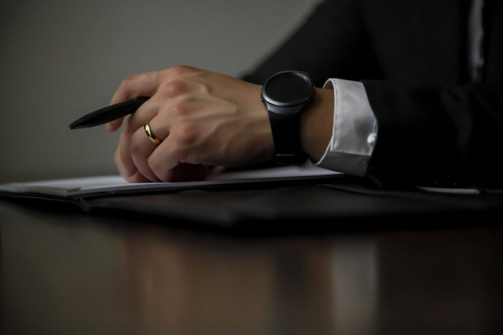 man sitting on table waiting on paper to be signed